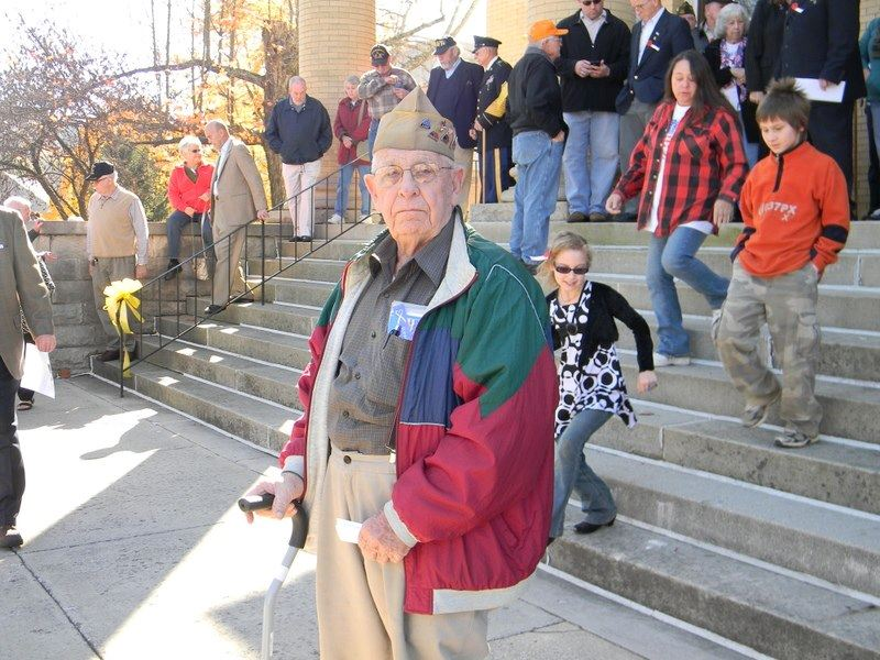Veteran with cane stands alone, while in background a crowd of people descend marble steps of Court House